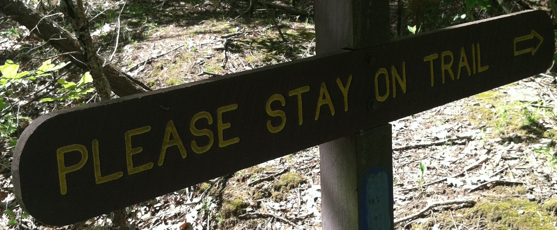 """PLEASE STAY ON THE TRAIL"" sign"